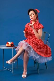 Het leuke pinupmeisje stellen met cupcakes