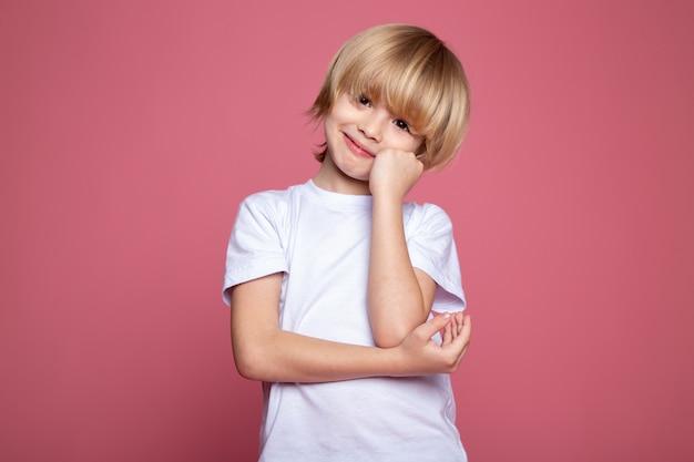 Het leuke schattige portret van de kindjongen in het witte t-shirt en op roze