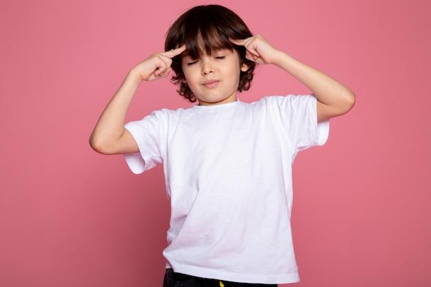 Het leuke schattige portret van de kindjongen in wit t-shirt en zwarte broeken op roze bureau