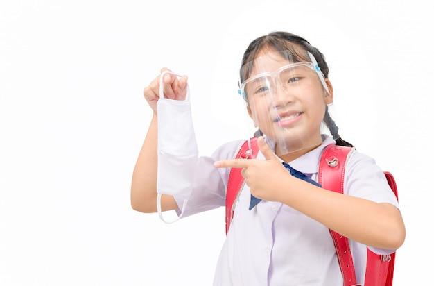 Het leuke schoolmeisje draagt eenvormig en gezichtsschild en wijst naar het geïsoleerde doekmasker