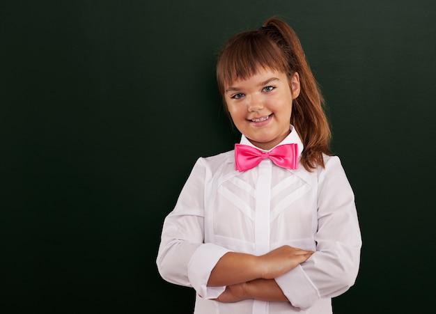 Het leuke schoolmeisje stellen voor bord