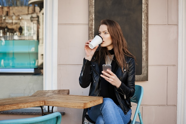Het leven in de wilde stad kost veel energie. aantrekkelijke doordachte en stijlvolle vrouwelijke toerist, caféterras zitten en koffie drinken