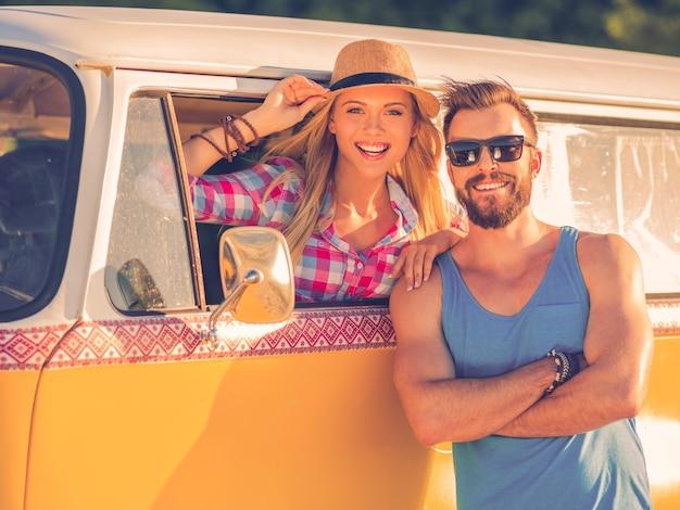 Het leven is beter als we samen zijn! vrolijke jonge vrouw die in een retro minibus zit en door het raam van het voertuig kijkt terwijl de man buiten staat en glimlacht
