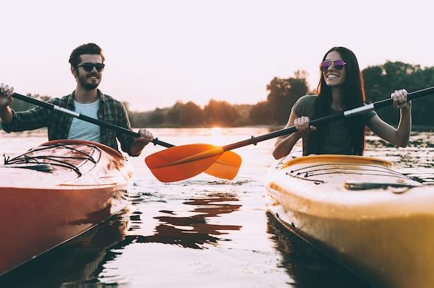 Het leven is beter op de rivier. vrolijk jong stel kajakken op de rivier samen met zonsondergang op de achtergronden