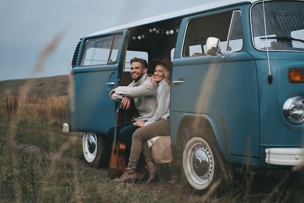 Het leven is een avontuur. mooie jonge paar wegkijken en glimlachen zittend in blauwe retro-stijl minibusje