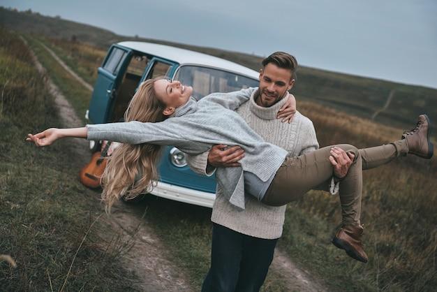 Het leven is geweldig knappe jonge man die zijn aantrekkelijke vriendin draagt en glimlacht terwijl hij in de buurt van het blauwe minibusje in retrostijl staat