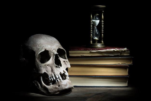 Het leven is kort concept. schedel en vintage zandloper op oude boeken en houten tafel