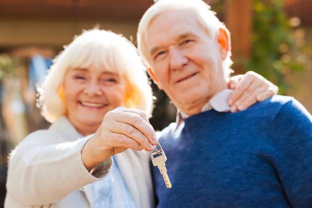 Het leven is nog maar net begonnen. gelukkig senior koppel hecht zich aan elkaar en glimlacht terwijl vrouw sleutels in haar hand houdt