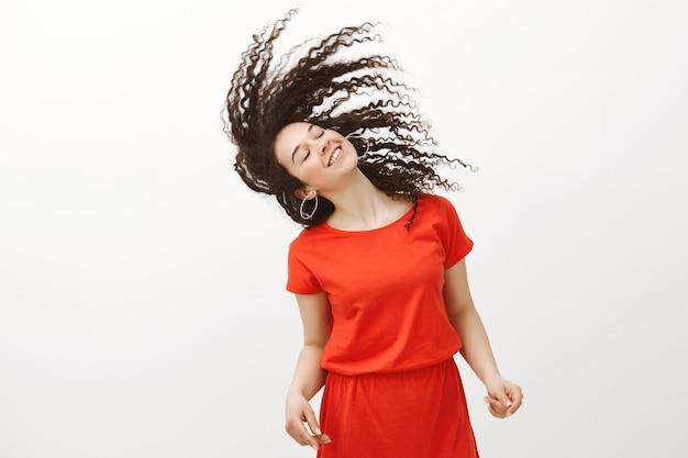 Het leven ten volle leven. gelukkig positieve aantrekkelijke vrouw in stijlvolle rode jurk