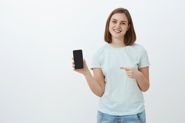 Het leven veranderde na deze telefoon. portret van vriendelijk ogende opgetogen charmante vrouw met kort bruin haar in casual licht t-shirt weergegeven: gsm-scherm en wijzend op smartphone glimlachen