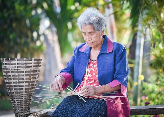 Het levens oude vrouw die van azië in huis werken
