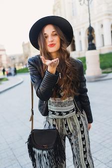 Het levensstijlportret van vrij vrolijke vrouw verzendt kus, lachend, genietend van vakantie in oude europese stad. street fashion look. stijlvolle lente-outfit.