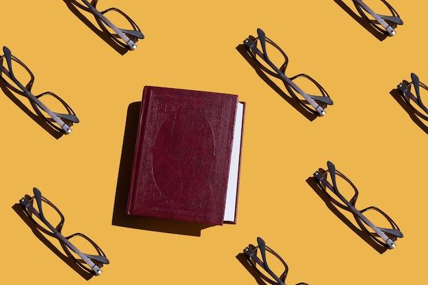 Het lezen van informatie en onderwijsconceptglazen en een boek op oranje achtergrond