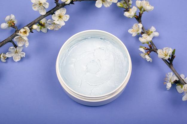 Het lichaam schrobt met takken van witte kersenbloemen op een violet close-up als achtergrond, lichaamsverzorgingproduct.