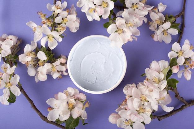 Het lichaam schrobt met witte bloemen op een violet achtergrond hoogste meningsclose-up. huidverzorging cosmetica, spa, schoonheid, het voorkomen van rimpels, huidreiniging