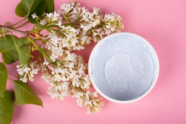 Het lichaam schrobt op een roze achtergrond met bloemen van lila hoogste meningsclose-up. huidverzorging cosmetica, schoonheid, spa.