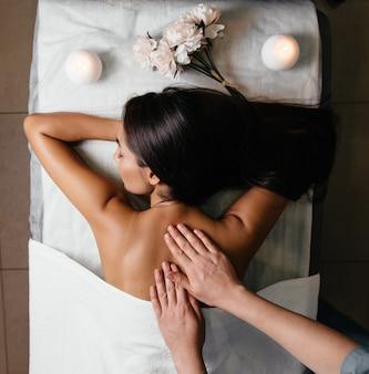 Het lichaam van de mooie aziatische vrouw terug en roze spijker op grijze achtergrond.