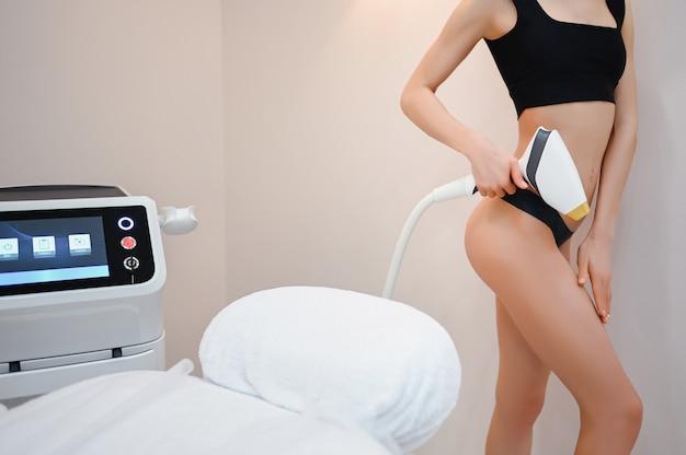 Het lichaam van de mooie geschikte vrouw met vlotte zachte huid in zwarte lingerie met het apparaat van laserapparaten dat in schoonheidssalon wordt geïsoleerd. ontharing en cosmetologie. epilatie spa concept. vrije ruimte voor tekstbanner