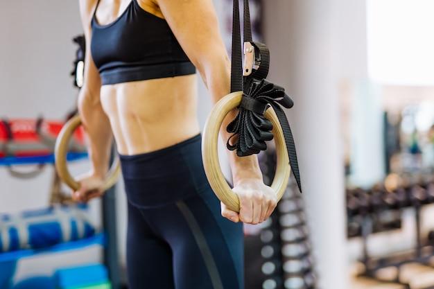 Het lichaam van de sportieve vrouw die gymnastiek- ringen in de gymnastiek houden.