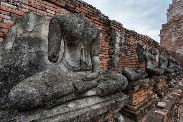Het lichaam van een stenen boeddhabeeld op een oud hek bij de chaiwatthanaram-tempel, thailand