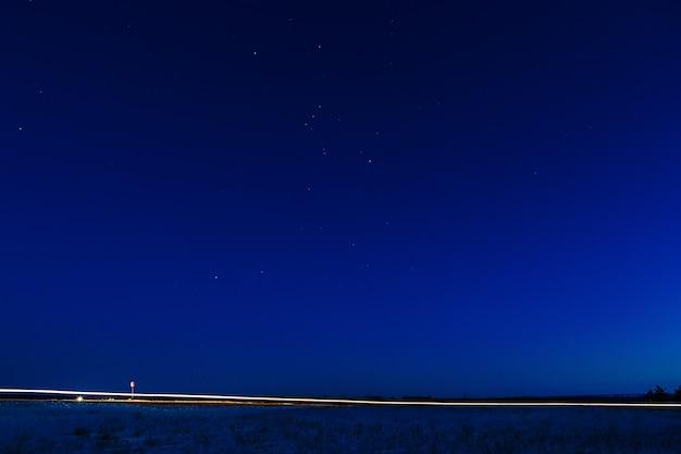 Het licht van de koplampen van een auto op een achtergrond van de sterrenhemel.