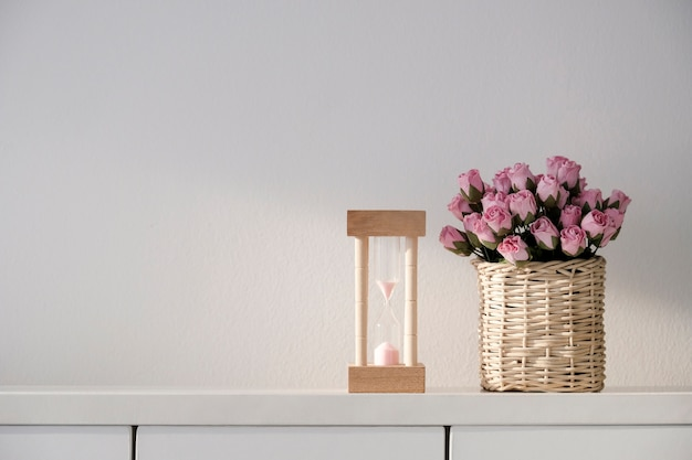 Het liefdeconcept zandloper en het roze document namen bloem in mand toe