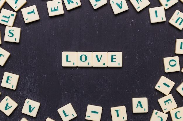 Het liefdewoord op zwarte die achtergrond wordt geschikt door graait brieven wordt omringd die