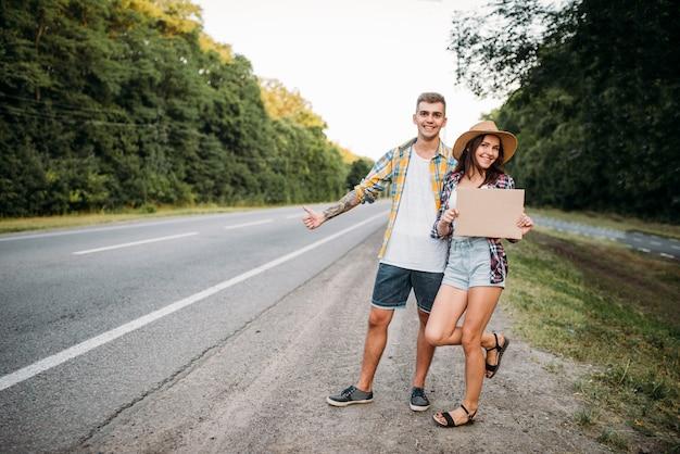 Het liftende paar houdt leeg karton met exemplaarruimte. liftend avontuur van jonge man en vrouw. gelukkige lifters op weg