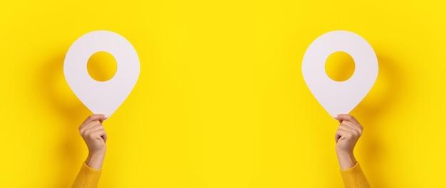 Het locatiesymbool in handen over gele achtergrond, panoramisch beeld