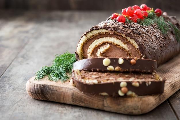 Het logboekcake van de chocolade yule met rode aalbes op houten exemplaarruimte