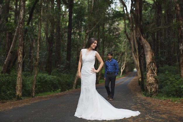 Het lopen van de jonge bruid en bruidegom in het bos