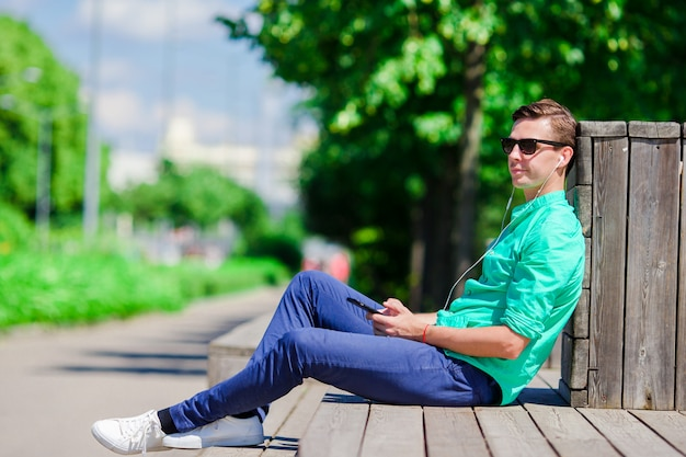 Het luisteren van de jongen muziek door smartphone op de zomervakantie