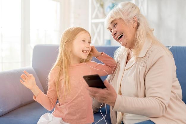 Het luisteren van de oma en van het meisje muziek op mobiel