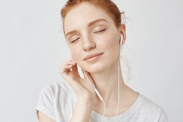 Het luisteren van de roodharige vrouw muziek in hoofdtelefoons met gesloten ogen.
