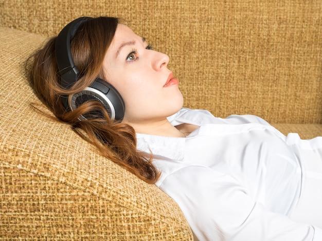 Het luisteren van de vrouw muziek met hoofdtelefoons, die op bank liggen