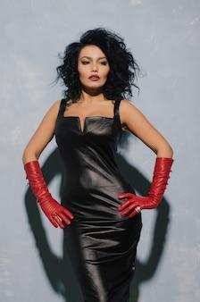 Het luxueuze aziatische vrouw stellen in zwarte leerkleding en rode handschoenen. dominante fetisj dame.