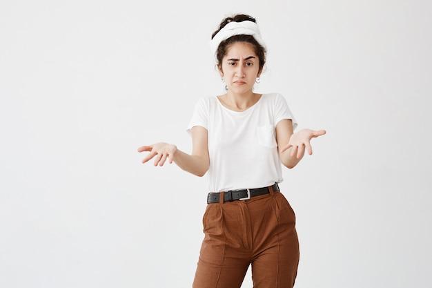Het maakt niet uit. clueless donkerharige vrouw gekleed in een wit t-shirt, lippen opjagend, schouders ophalend, starend van woede nadat ze iets verkeerds had gedaan maar zich niet schuldig voelde