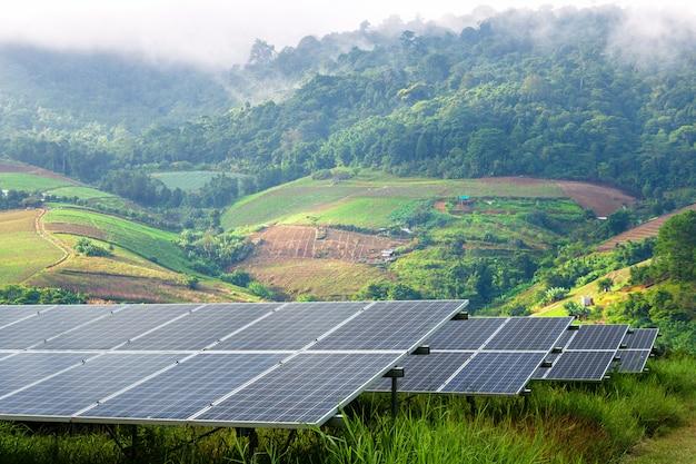 Het machtszonnepaneel op klein bergachtig dorp en de mist zijn schoonheid op gezichtspunt, alternatief schoon groen energieconcept