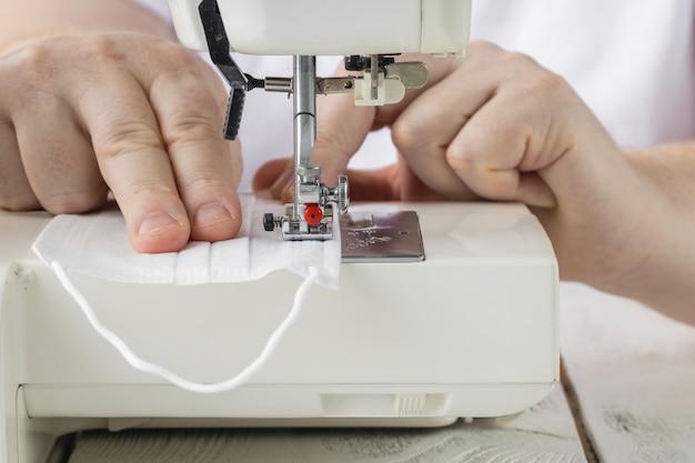 Het maken van beschermende medische maskers van met de hand gemaakt coronavirus naaien. maak zelf geen afval herbruikbaar van het masker.