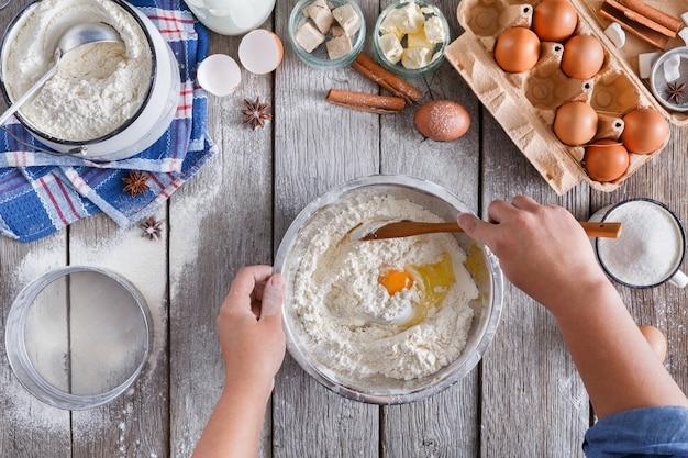 Het maken van deeg bovenaanzicht. roer boven de bakker de eidooier met bloem. koken ingrediënten voor gebak op rustiek hout, culinaire lessen of receptconcept.