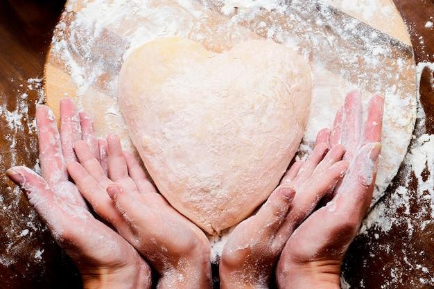 Het maken van deeg van eieren en melk. hartvormig deeg met vrouwelijke en kindhanden. koken en thuis concept