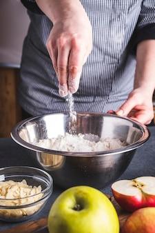 Het maken van deeg voor appeltaart door vrouwelijke handen. de kok mengt ingrediënten voor appeltaart.