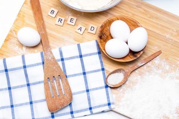 Het maken van deeg voor brood of zelfgemaakt gebak. ingrediënten op een houten tafel. opschrift: brood
