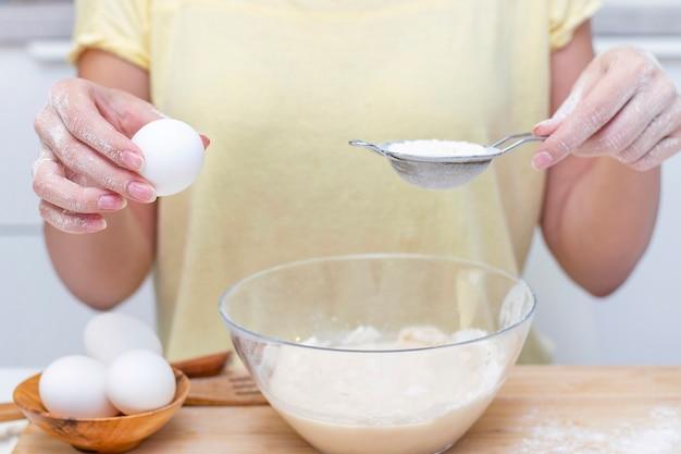 Het maken van deeg voor brood of zelfgemaakt gebak. ingrediënten op het bureau. vrouwelijke handen met een ei