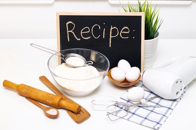 Het maken van deeg voor brood of zelfgemaakt gebak. ingrediënten op tafel. receptenbord