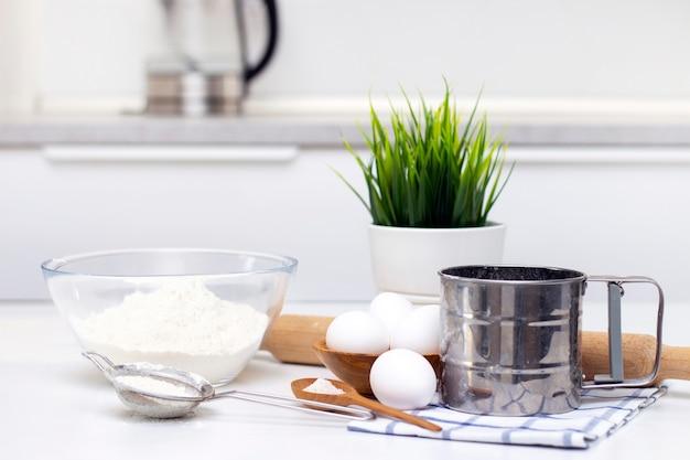 Het maken van deeg voor brood of zelfgemaakt gebak. ingrediënten op tafel. tegen de achtergrond van een lichte, moderne keuken