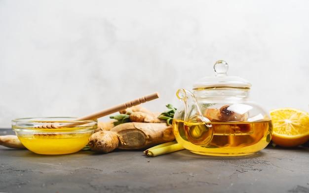 Het maken van gezonde antioxidant en ontstekingsremmende gemberthee met verse gember, citroengras, salie, honing en citroen op donkere achtergrond met kopie ruimte.