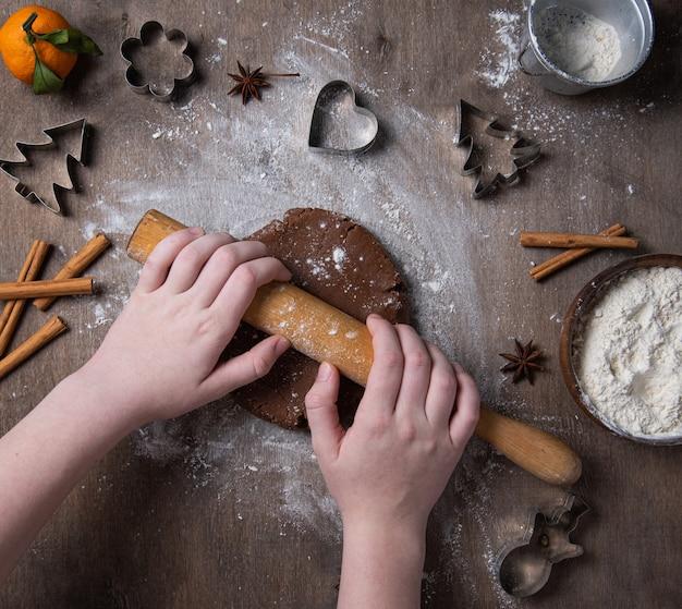 Het maken van kerst gember chocoladekoekjes met handen op oude tafel.