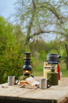 Het maken van koffie of thee op draagbare gasfornuis op de aard. reizen, avontuur, kampeerspullen, items buitenshuis.