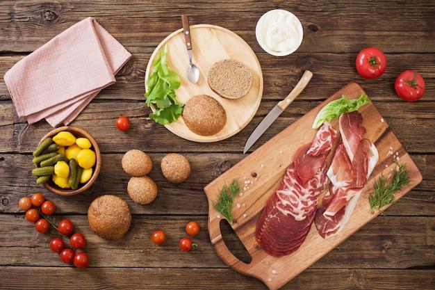 Het maken van sandwiches met vlees en worst op houten tafel